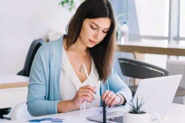 Foto de uma estudante elaborando o seu currículo para primeiro emprego