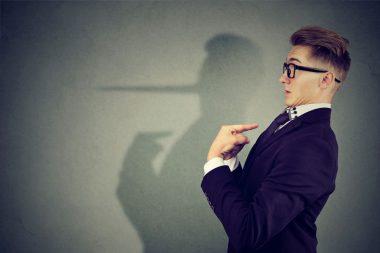 Foto de um executivo onde sua sombra faz alusão ao pinóquio