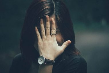 Foto de uma mulher com vergonha escondendo o rosto com a mão