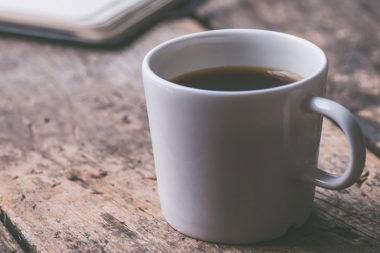 Foto de uma xícara de café sobre uma mesa de madeira