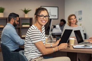 Foto de uma mulher sorrindo no escritório com colegas de trabalho