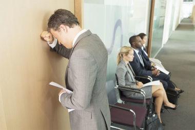 Foto de um homem lamentando após ser reprovado na entrevista de emprego