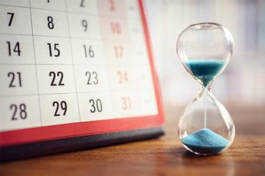Foto de uma ampulheta e um calendário