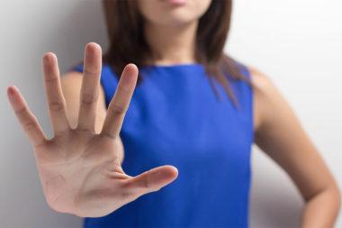 Foto de uma mulher sinalizando pare