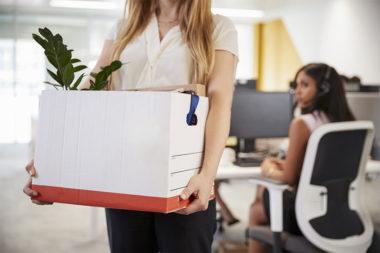 Foto de uma mulher carregando suas coisas ao deixar a empresa