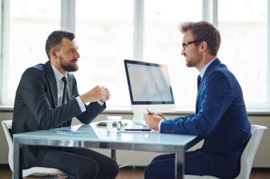 Foto de uma entrevista de emprego com candidato e recrutador