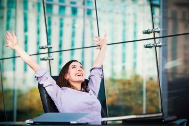 Foto de uma mulher feliz com os braços para cima em seu emprego