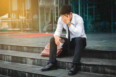 Foto de um homem desempregado de cabeça baixa