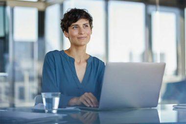 Foto de mulher pensativa na frente do notebook