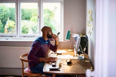 Foto de profissional trabalhando no computador em casa (home office)