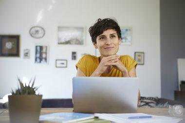 Foto de uma mulher otimista na frente de um notebook