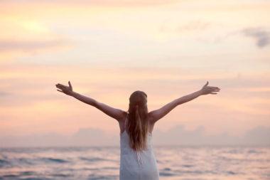 Foto de uma mulher de braços abertos na praia