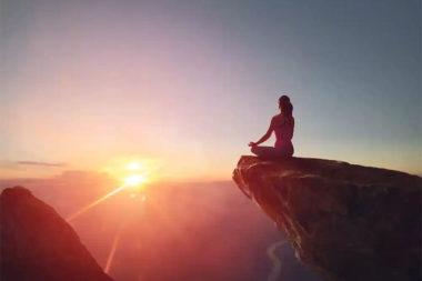 Foto de uma mulher admirando o pôr do sol