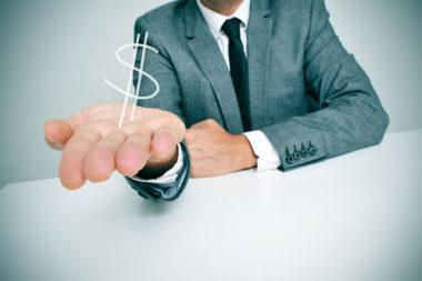 Foto de um executivo com um cifrão na palma da mão