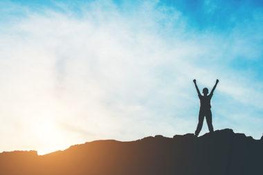 Foto de uma pessoa feliz no topo de uma montanha