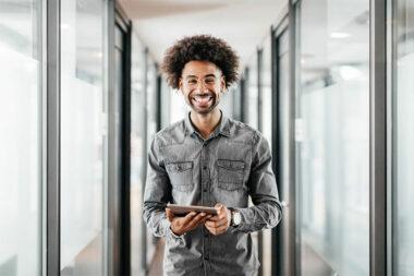 Foto de um profissional sorrindo com um tablet na mão